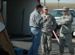 Daryl Beam, protection services specialist, discusses the decontamination shelter and its features with National Guard team members.
