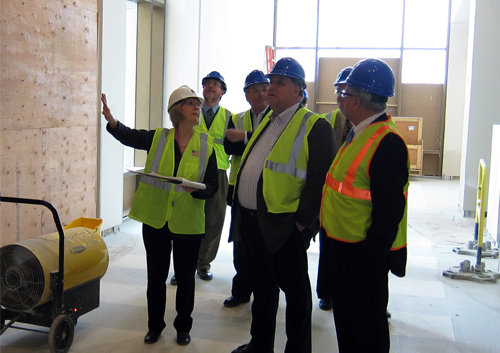 Claudia Berg (left) explains the new exhibit space to Andrew Serri (center), Dennis Hill (behind Serri) and other State Historical Society and Foundation staff.