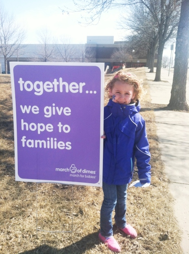 Germain Krueger's daughter, Cortney, stands next to a March of Dimes sign during the March for Babies event, which took place at the Bismarck Civic Center on April 6. Krueger and the Basin Electric Team raised $2,211, which will go toward research that could prevent birth defects and fight the respiratory syncytial virus.