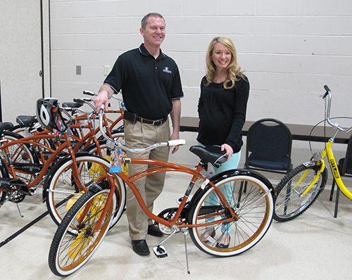 Wes Engbrecht, Capital Electric director of communications and public relations, and Jen Holen, Basin Electric event planner and charitable giving coordinator, stand next to one of the bikes recently purchased for the Bike Sharing Program at United Tribes Technical College.
