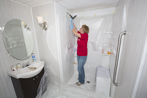 A Wells Fargo representative, who also was among community members who reached out to Cliff and Clara Stack through Rebuilding Together, adjusts the showerhead in the couple's new bathroom.