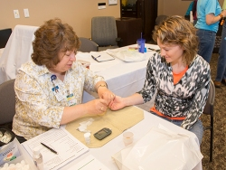 Donna Amundson, director of Sanford Diabetes Care, tests the blood sugar of Whitney Fischer, financial analyst II, during Basin Electric's Safety & Wellness Fair on Wednesday.