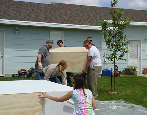 Engineering Document Coordinator Tiffany Bailey paints while Senior Civil Engineer Dave Erickson (front left); Myron Steckler, generation resource project manager; GIS Technician Alan Dale (front right); Civil Engineer Shane Vasbinder (back left); and Civil Engineer Cory Bauer (back right) move one of the wooden levels that will make up the float.