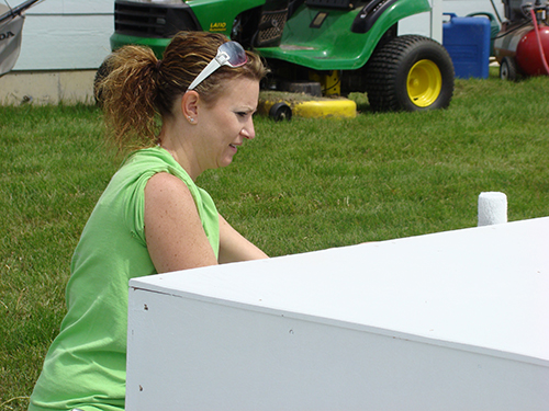 Senior Administrative Assistant Shawnel Huber paints a box tier.