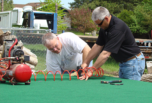 Designer Ryan Lang (left) and Lead Surveyor Matt Weeks help assemble Basin Electric's 4th of July float on June 6.