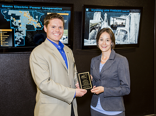 On behalf of Basin Electric, Auditor II Shawna Piatz accepts an appreciation plaque from Jordan Neufeld, CPA for the North Dakota Community Foundation, for the cooperative's sponsorship of the Great Plains Young Professionals Summit.