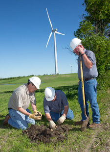 Basin Electric employees (from left) Kevin Solie, Kyle Opp and Darrell Schulz plant a replacement tree on private land near PrairieWinds 1 south of Minot, ND.