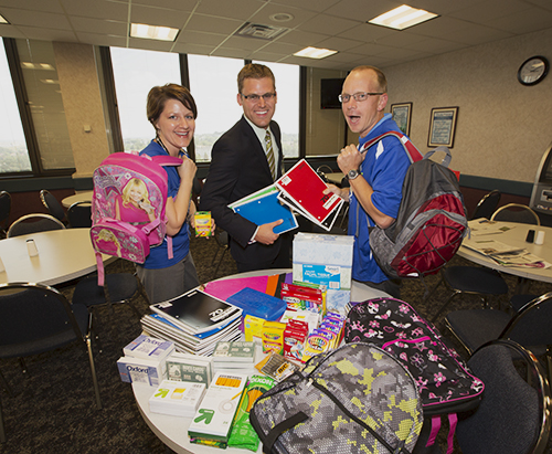 "BE Involved members Sheila Renner, Dain Sullivan and Mike Zimmerman huddle next to a pile of school supplies that Basin Electric employees donated toward ""Fill the Bus,"" a program aimed at helping families who can't afford certain necessities when back-to-school shopping."
