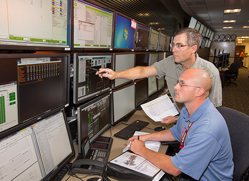 Joe Fiedler (standing), operations maintenance supervisor, goes over the screens with Shawn Meissel, distributed generation service dispatcher.