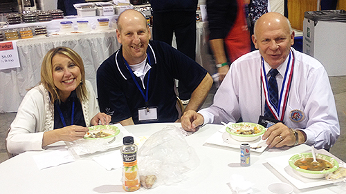 Verendrye General Manager Bruce Carlson (right) joins Ellen Holt, Basin Electric vice president of Human Resources, and her husband Brandon in eating a bowl of stew at Høstfest.