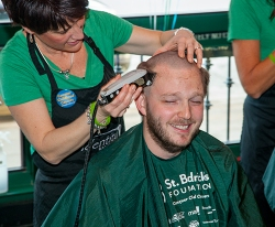 St. Baldrick's participant Josh Douglas chuckles during his haircut at Blarney Stone Pub.