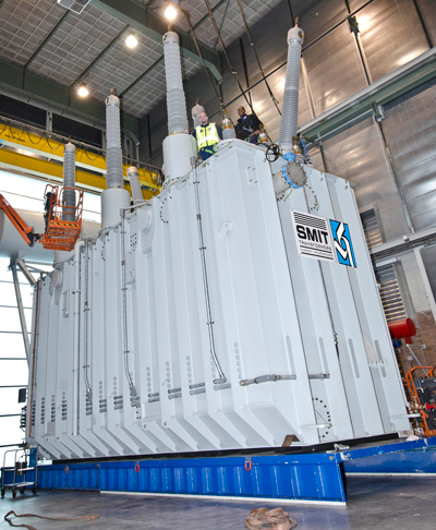 Look on top: Basin Electric employee Brennon McKenzie and a factory employee stand atop a brand new transformer in Nijmegen, Netherlands.