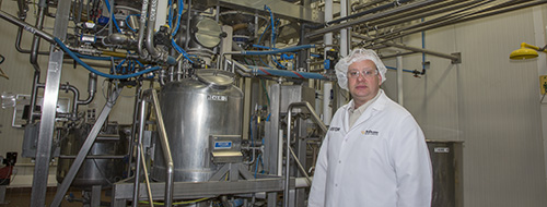 At the start of a tour, John Wilhelm, plant manager for BoDeans Baking Group in Le Mars, IA, stands near cone processing equipment.