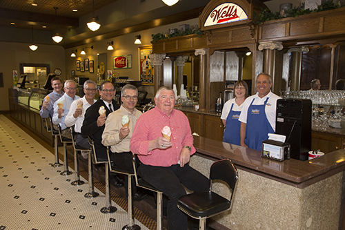 (Sitting, from left): Matt Washburn, Kent Pauling, Neal Adler, Scott Langel, Lyle Korver and Jim Henrich enjoy ice cream cones at the Blue Bunny Ice Cream Parlor in Le Mars, IA. The group, which was served the tasty treats by Gary Susemihl, parlor manager of 12 years, and fellow employee Branda Phelan, were among those who played a key role in shaping a development package to keep the Wells corporate headquarters in the community.