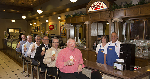 (Sitting, from left): Matt Washburn, Kent Pauling, Neal Adler, Scott Langel, Lyle Korver and Jim Henrich enjoy ice cream cones at the Blue Bunny Ice Cream Parlor in Le Mars, IA. The group, which was served the tasty treats by Parlor Manager Gary Susemihl and fellow employee Brenda Phelan, were among those who played a key role in shaping a development package to keep the Wells corporate headquarters in the community.