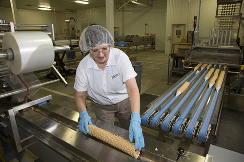 Pam Gleiser collects freshly made waffle cones at the BoDeans Baking facility in Le Mars, IA.