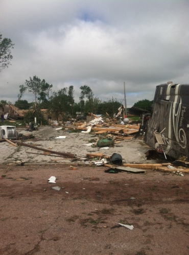 A cement slab marks the spot where a 40-foot by 60-foot steel shed once sat. Owned by Heumiller's neighbor, it housed an RV motor home (seen on the right-side of photo), tipped on its side by the tornado.