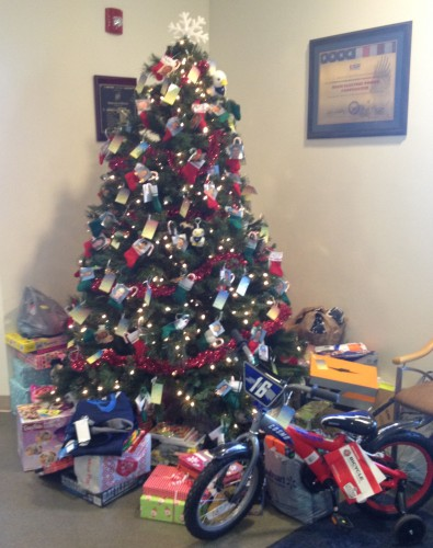 Gifts collected for two families with a total of 11 children surround the tree at Dry Fork Station.