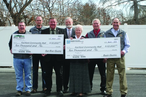 Sun River Electric Cooperative board members and employees present checks to the Fairfield Community Parking lot project. From left to right: Ross Oveson, SREC employee and Fairfield Lions Club; Chris Christensen, SREC employee and Fairfield Lions Club; John Burgmaier, SREC director; Scott Odegard, SREC manager; Roberta Rohrer, SREC secretary/treasurer and Basin Electric director; Brad Bauman, SREC employee and Fairfield Lions Club; Robert Anderson, SRECE employee and Fairfield Lions Club.