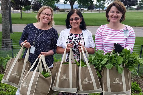 Employees hold bags of first garden harvest