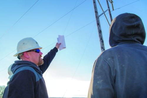 Dustin Gullickson, Basin Electric lead lineman (left), reviews the maintenance task with Journeyman Lineman Brian Lakoduk.
