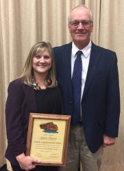 Angela Magstadt, Basin Electric staff writer, accepting North Dakota Water Wheel award from Mike Dwyer, North Dakota Water Users executive vice president.