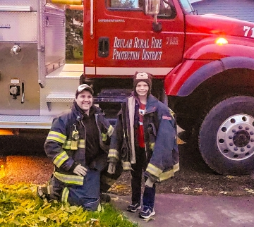 Bryce Brady, a fellow Beulah firefighter and lab technician at Dakota Gasification Company, poses with Beulah Elementary School student Jacob Perry, who won the honor of riding to school in a fire truck.