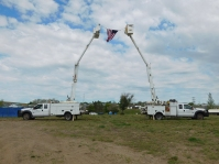 Bucket trucks displayed the U.S. flag as symbolism that we're all in this together as a co-op family.