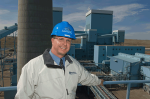 Man standing in front of power plant wearing a hard hat